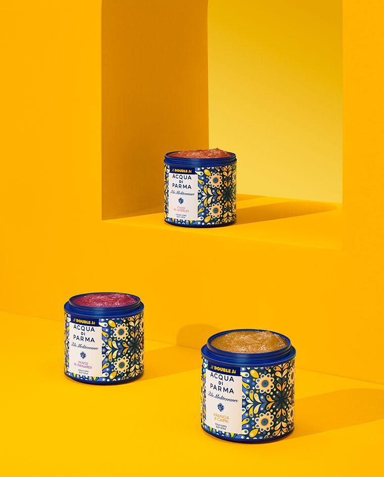 acqua di parma and la double j body scrub against a yellow background