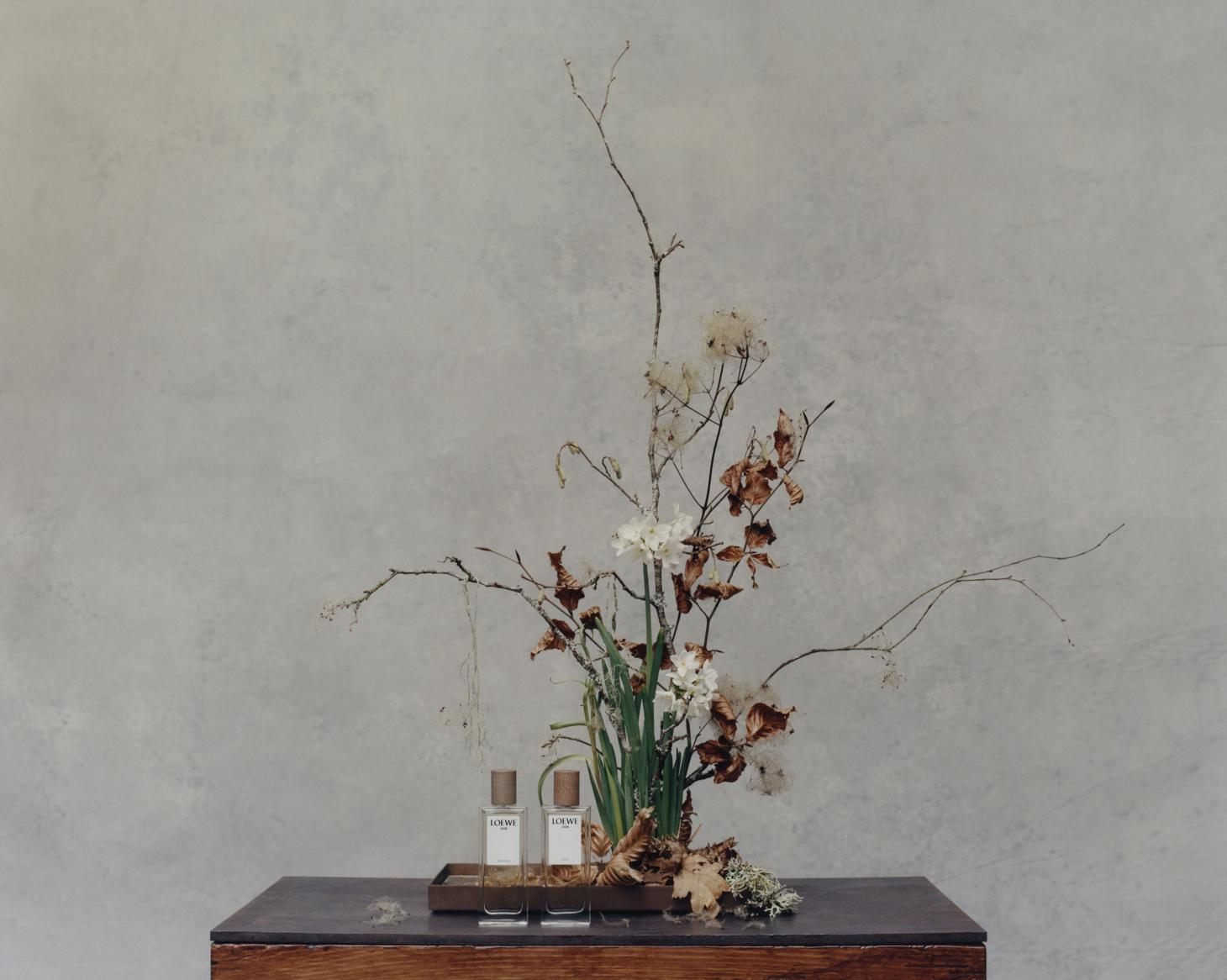 tyler mitchell photograph of loewe perfumes next to flower arrangement against light blue background