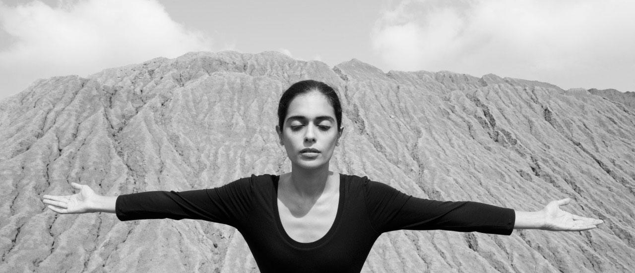 woman extending her arms in front of hill of sand