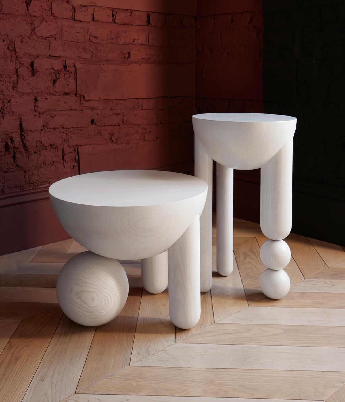 white curved marble tables against brick wall