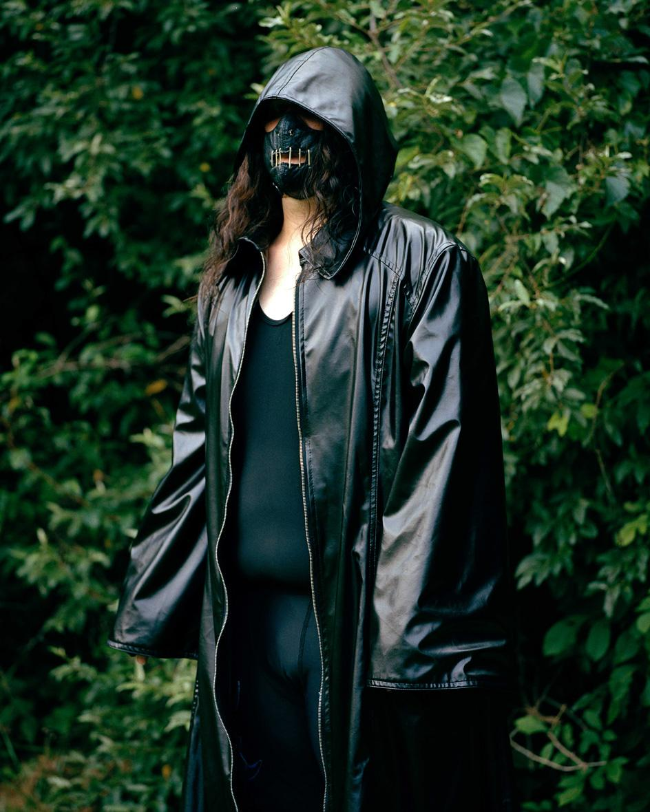 Photograph of person wearing mask and black coat against natural green backdrop