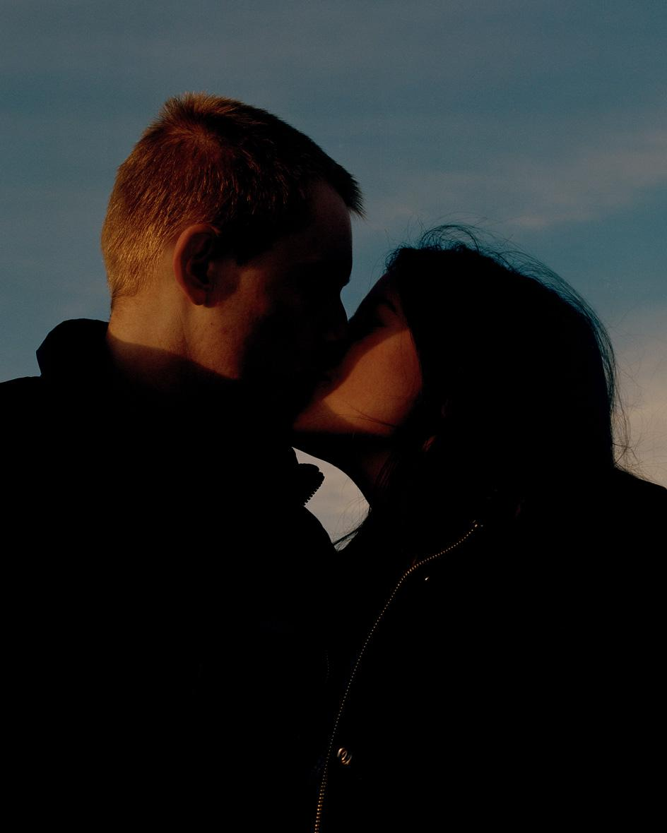 Photograph of a man and a woman in shadow, kissing