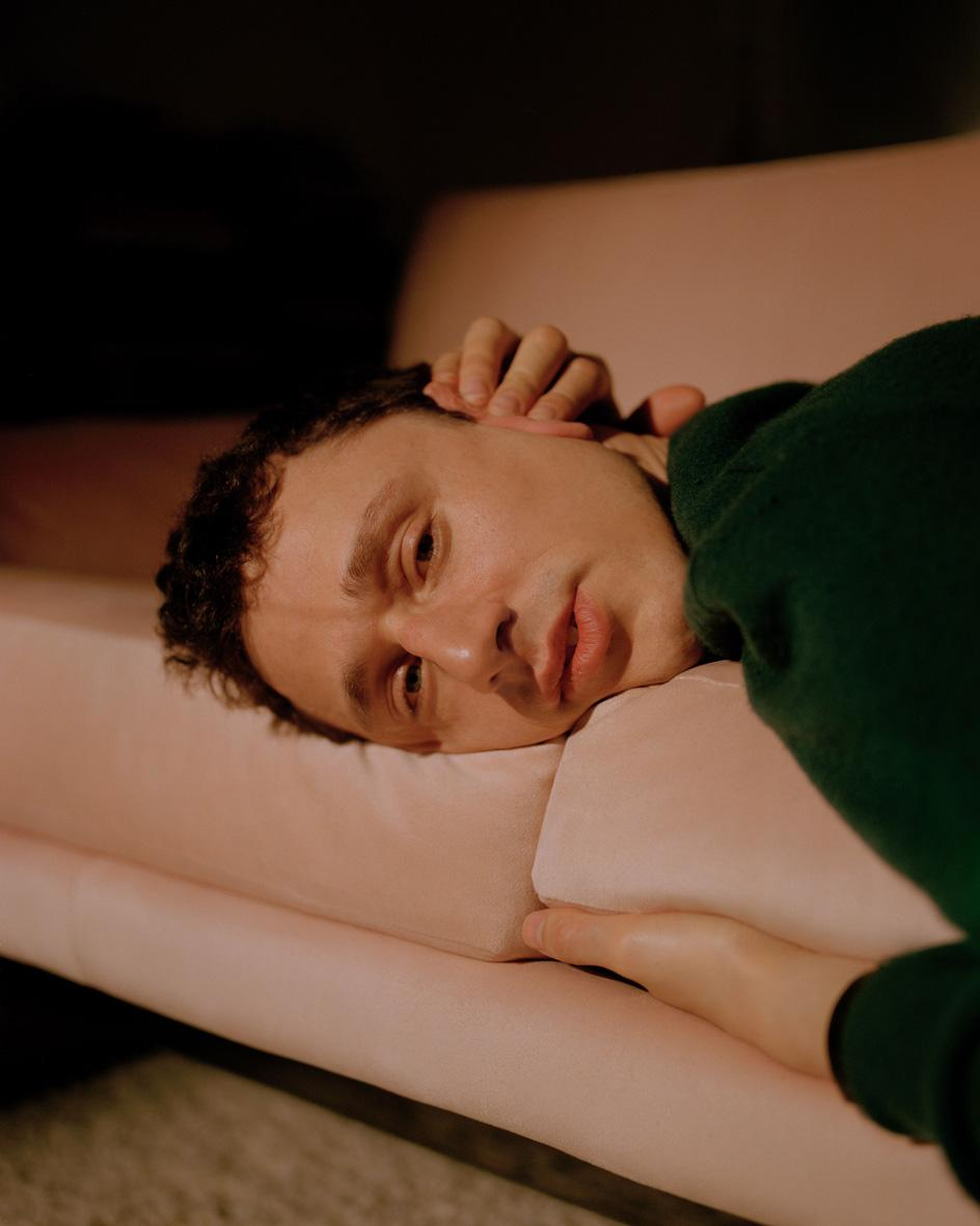 Close-up portrait of man's face, lying on pale couch