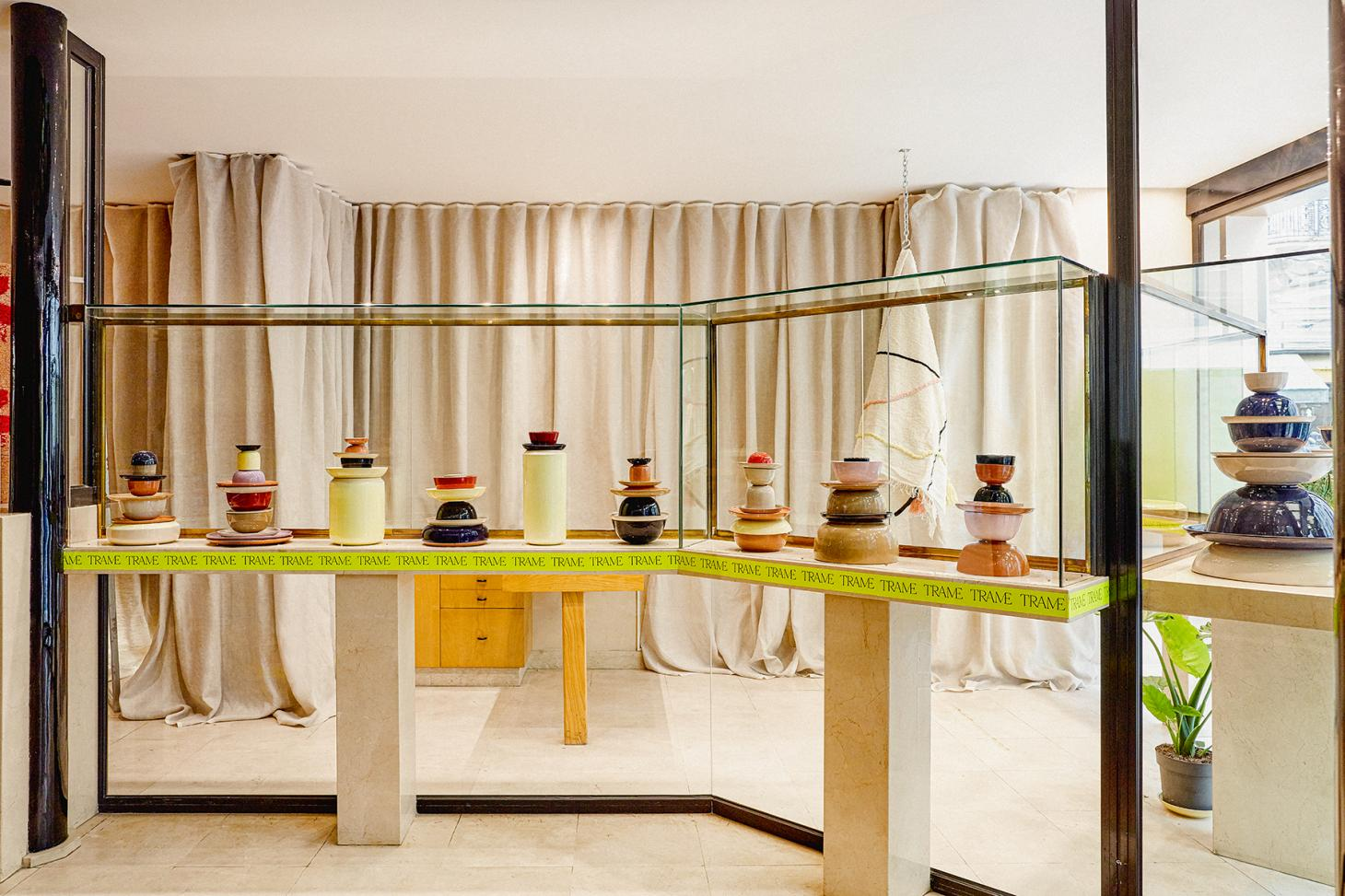 The interior of Paris store Trame, featuring a canvas curtain on the wall and a marble and wooden display structure with stacks of ceramic vessels in different colours