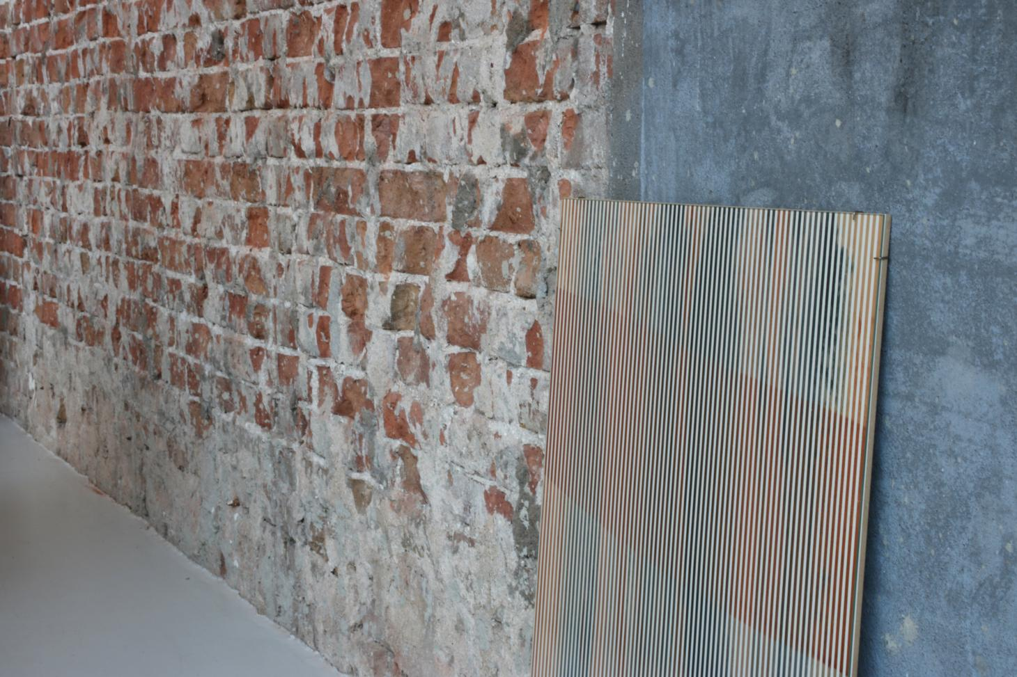Brick wall with panel displaying striped wallpaper from the living colour project by Buro Belen