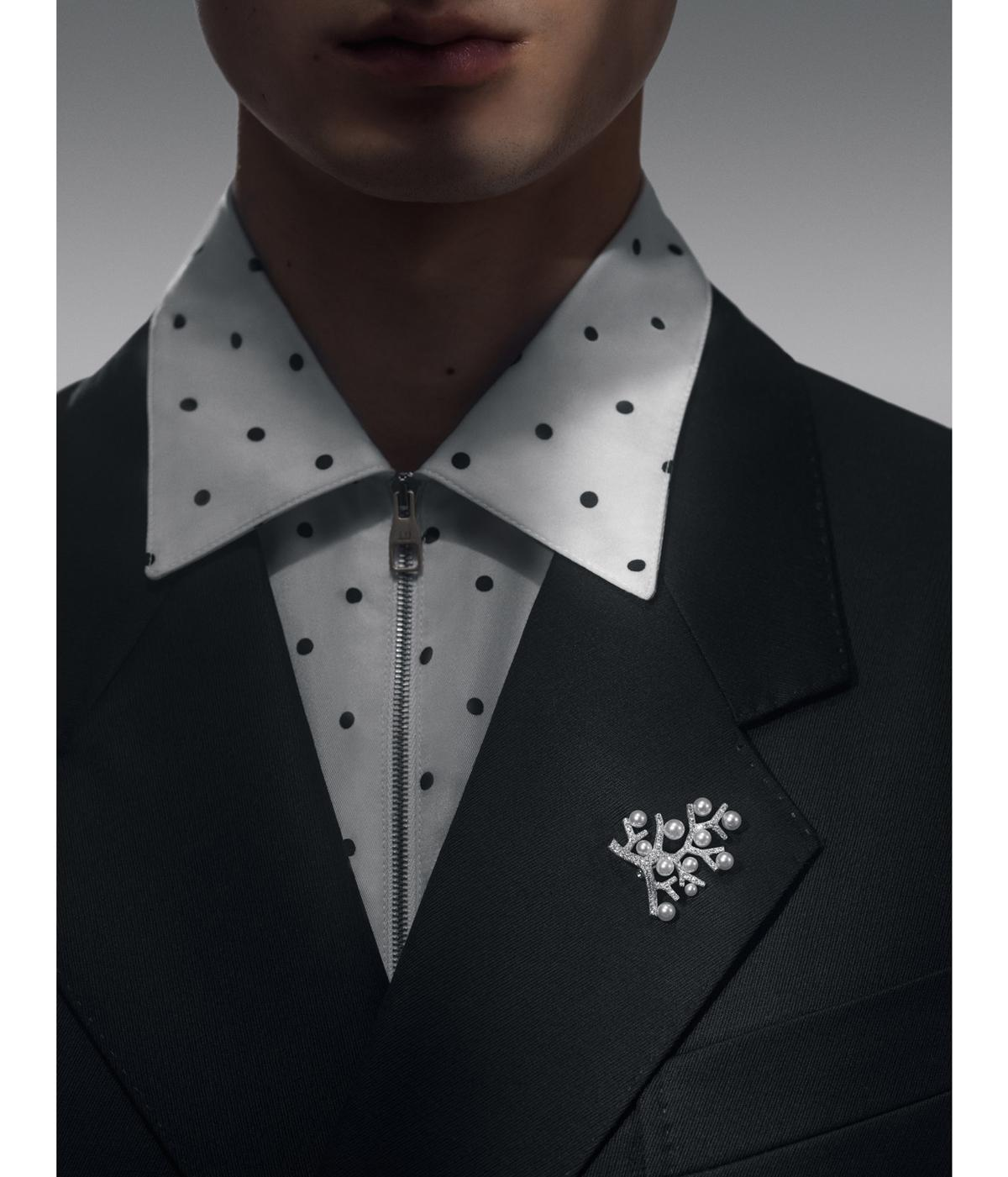 Man wearing pearl brooch and spotted shirt