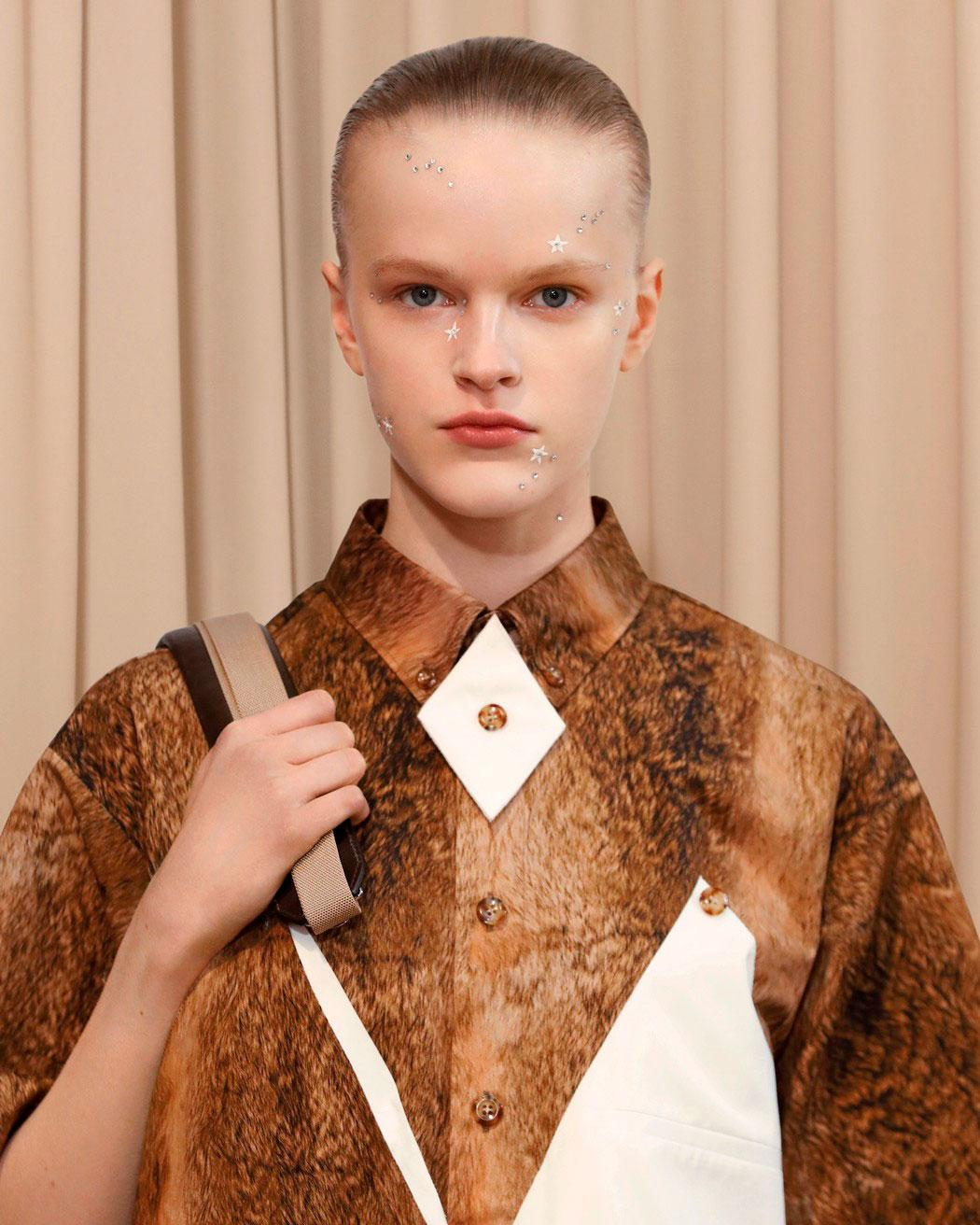 Burberry beauty A/W 2021 show showing model with slicked back hair and silver stars on her face