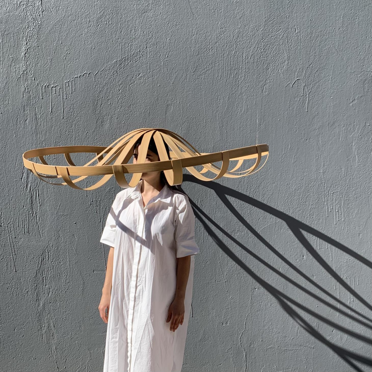 A model wearing a white dress and an oversized straw hat desinged by Stephen Burks