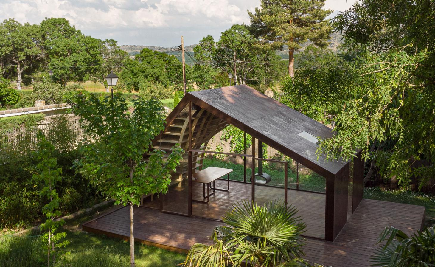 Cabin with wood roof and glass wall in a garden
