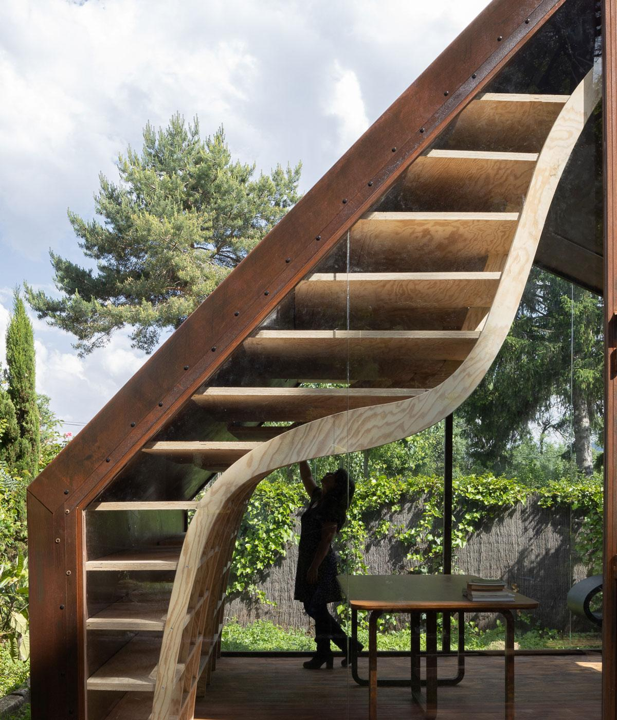 A curving wooden bookcase against glass window