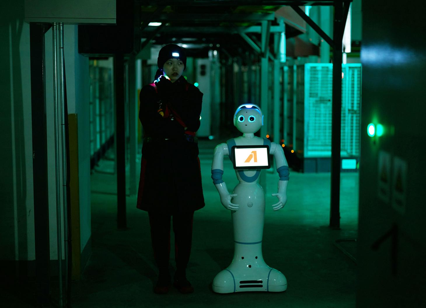 A young woman stood next to a robot in a dark alleyway