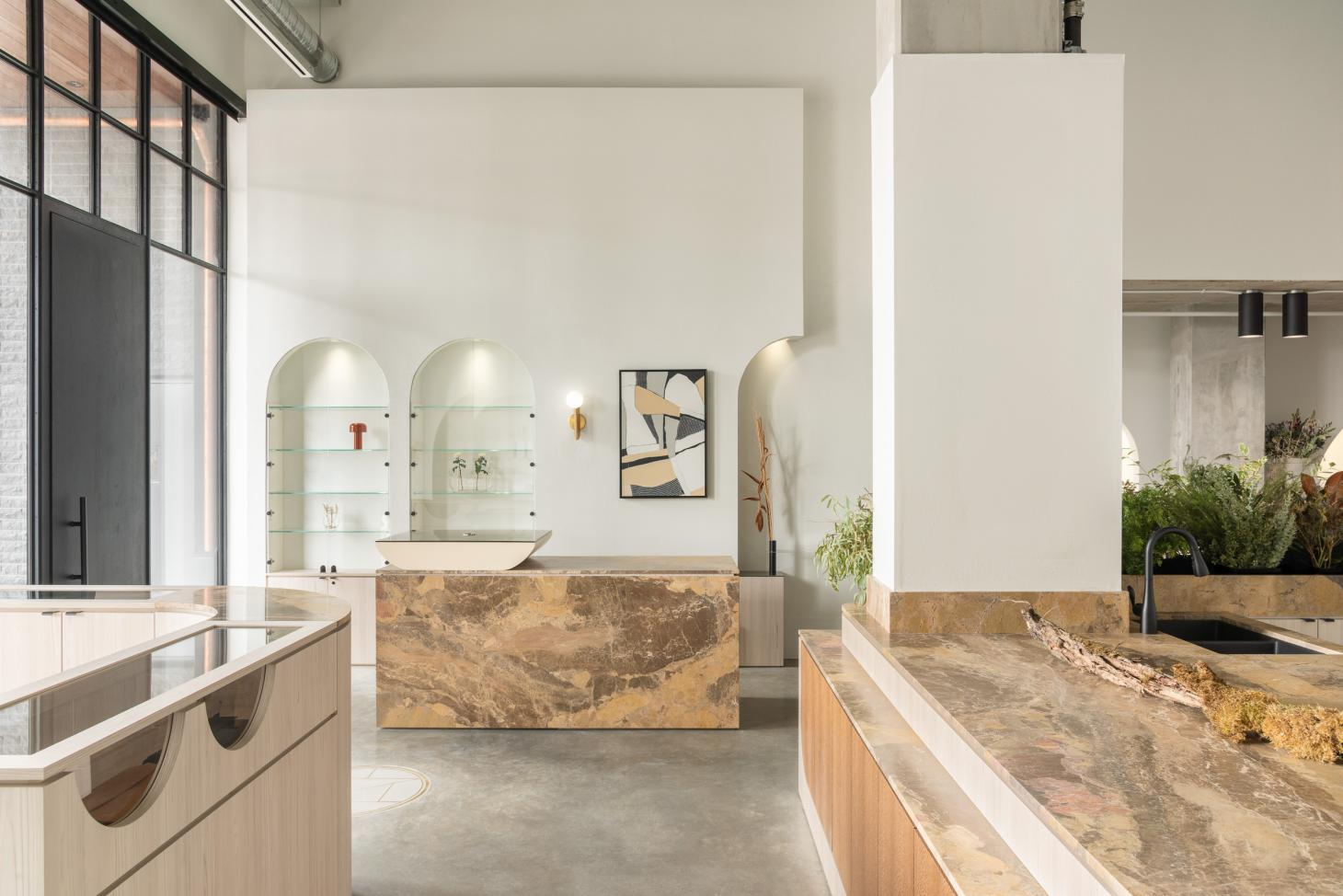 Cadine shop interior with concrete floor and white walls, furniture in granite and ash wood. Two alcoves with glass shelves are visible on the back wall