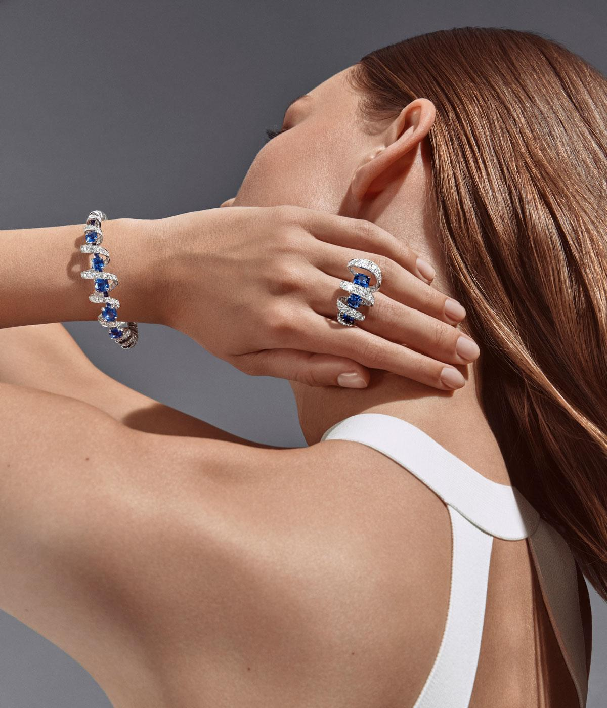Woman wearing a blue and diamond wirl ring and bracelet