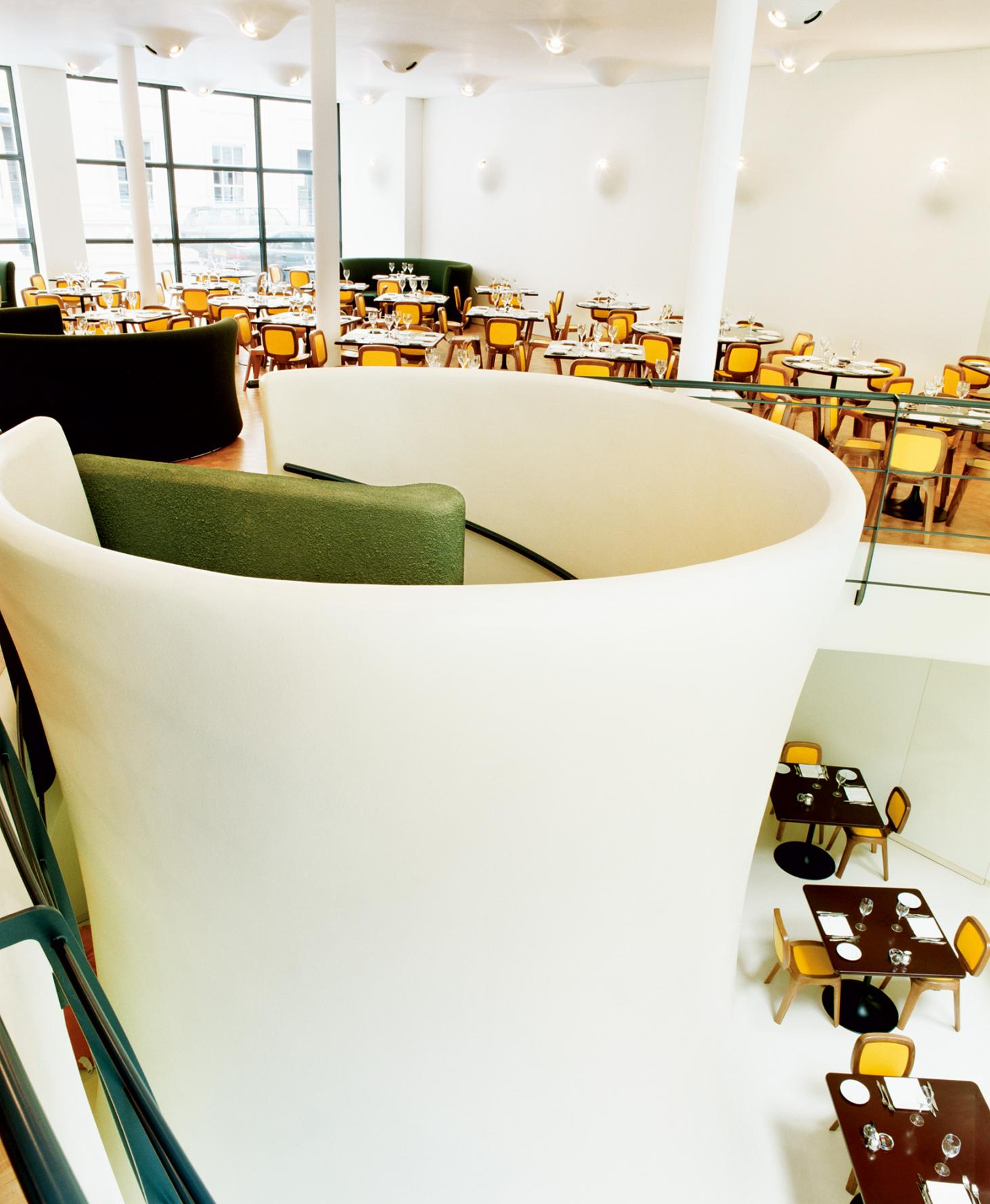 Interior of Coast Restaurant by Marc Newson with green banquets and yellow chairs