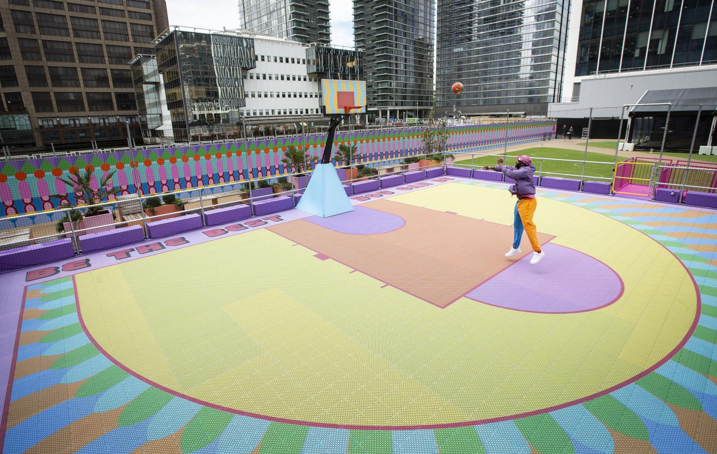 Yinka Ilori playing basket in his colourful court in Canary wharf, London