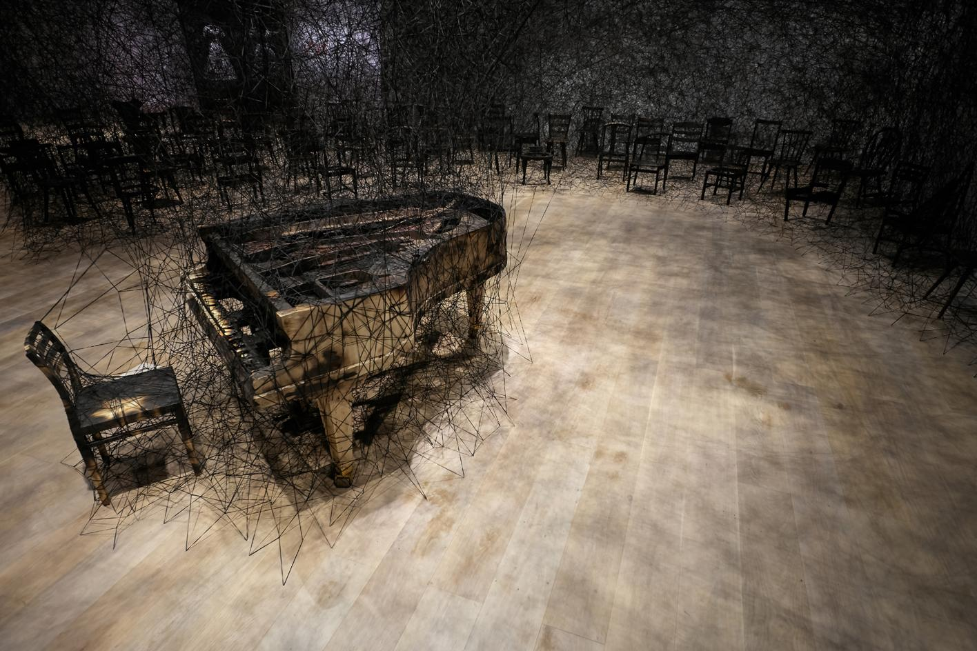 Chiharu Shiota's installation, In Silence at the Mori Art Museum in Tokyo, comprising a black Alcantara thread emanating from a burnt piano and chair