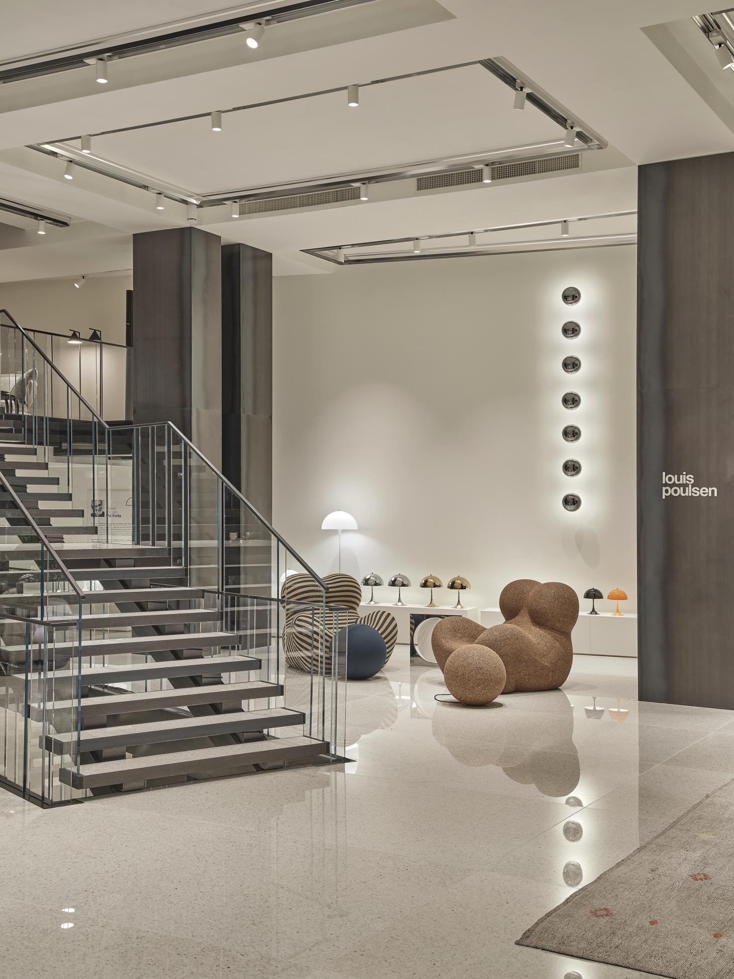 D Studio Milano with staircase leading to the first floor and Gaetano Pesce's armchairs for B&B Italia on one side