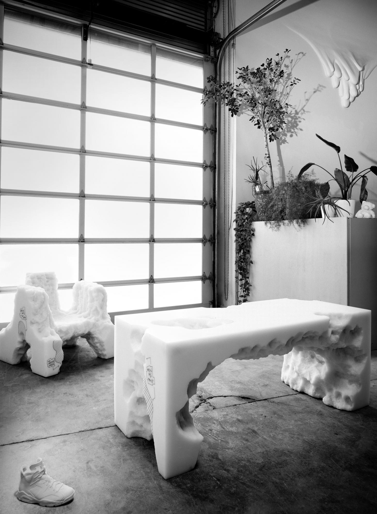 Black and white photograph of Daniel Arsham furniture, including a white resin table and chair whose design looks like eroded rock