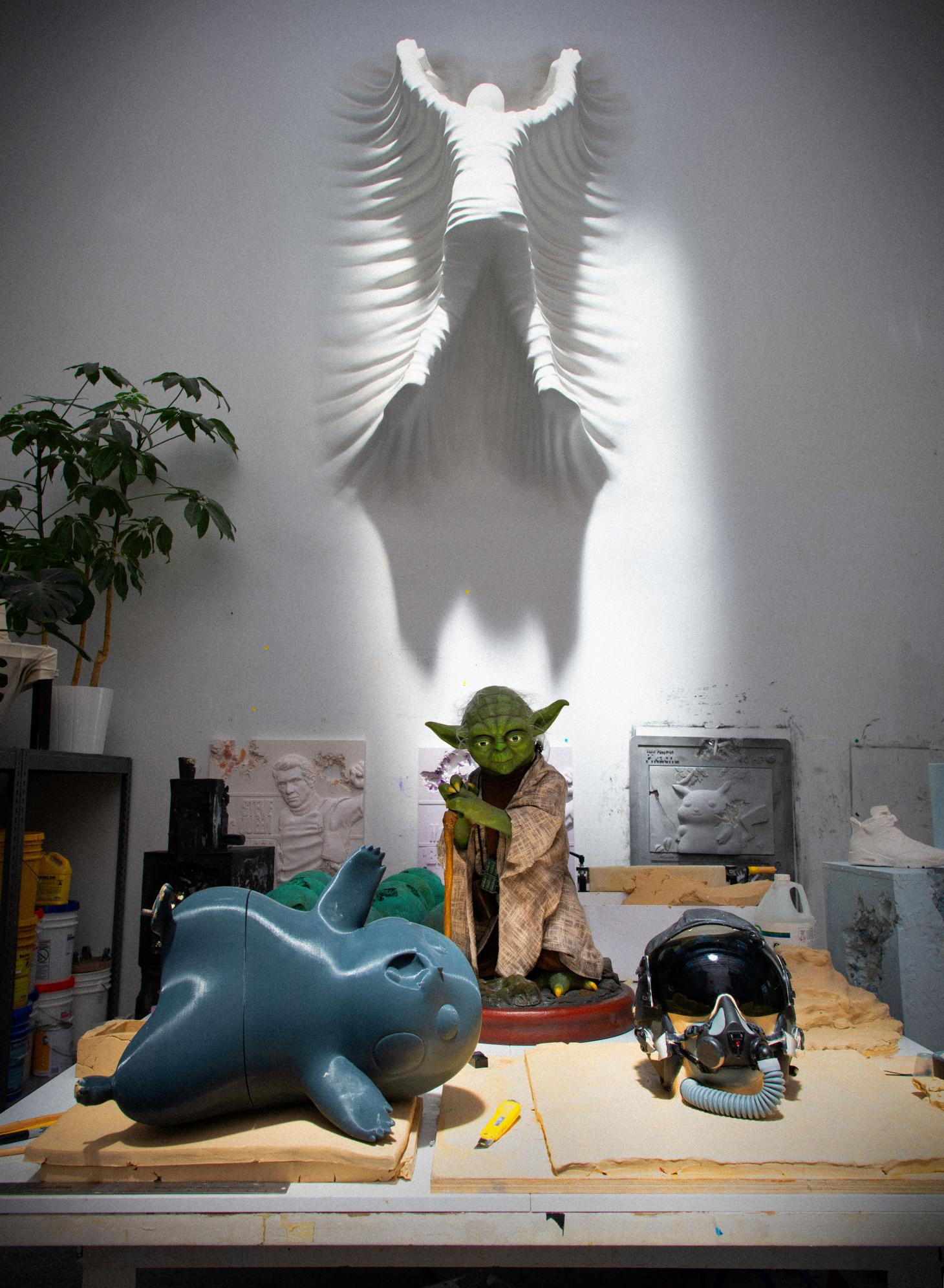 A desk at Daniel Arsham's studio with a 3D printed Pikachu model and a Yoda statue