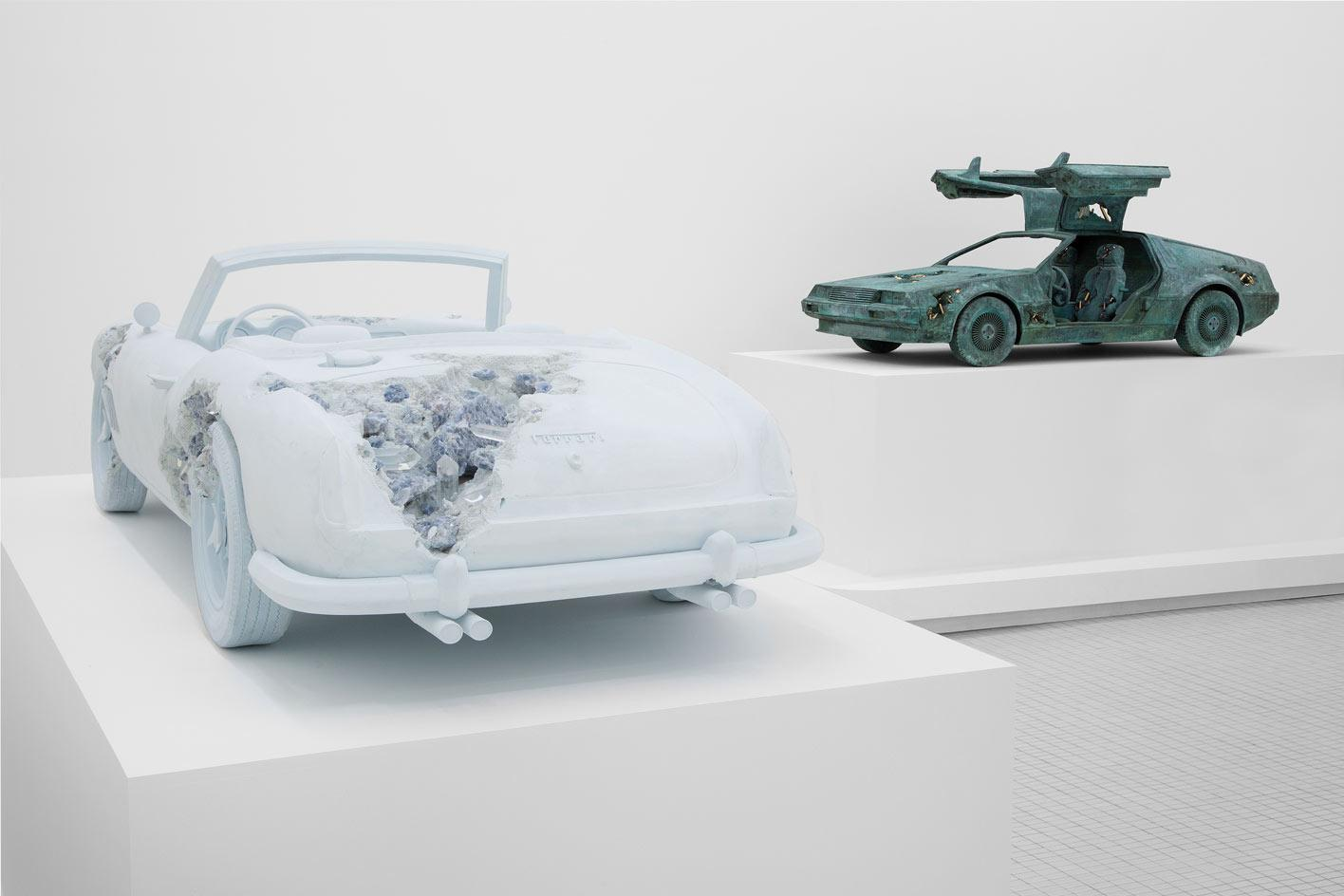 Installation view of Daniel Arsham, 'Turning Wrenches', featuringcar sculptures of a Ferrari (left) andDMC Delorean (right)