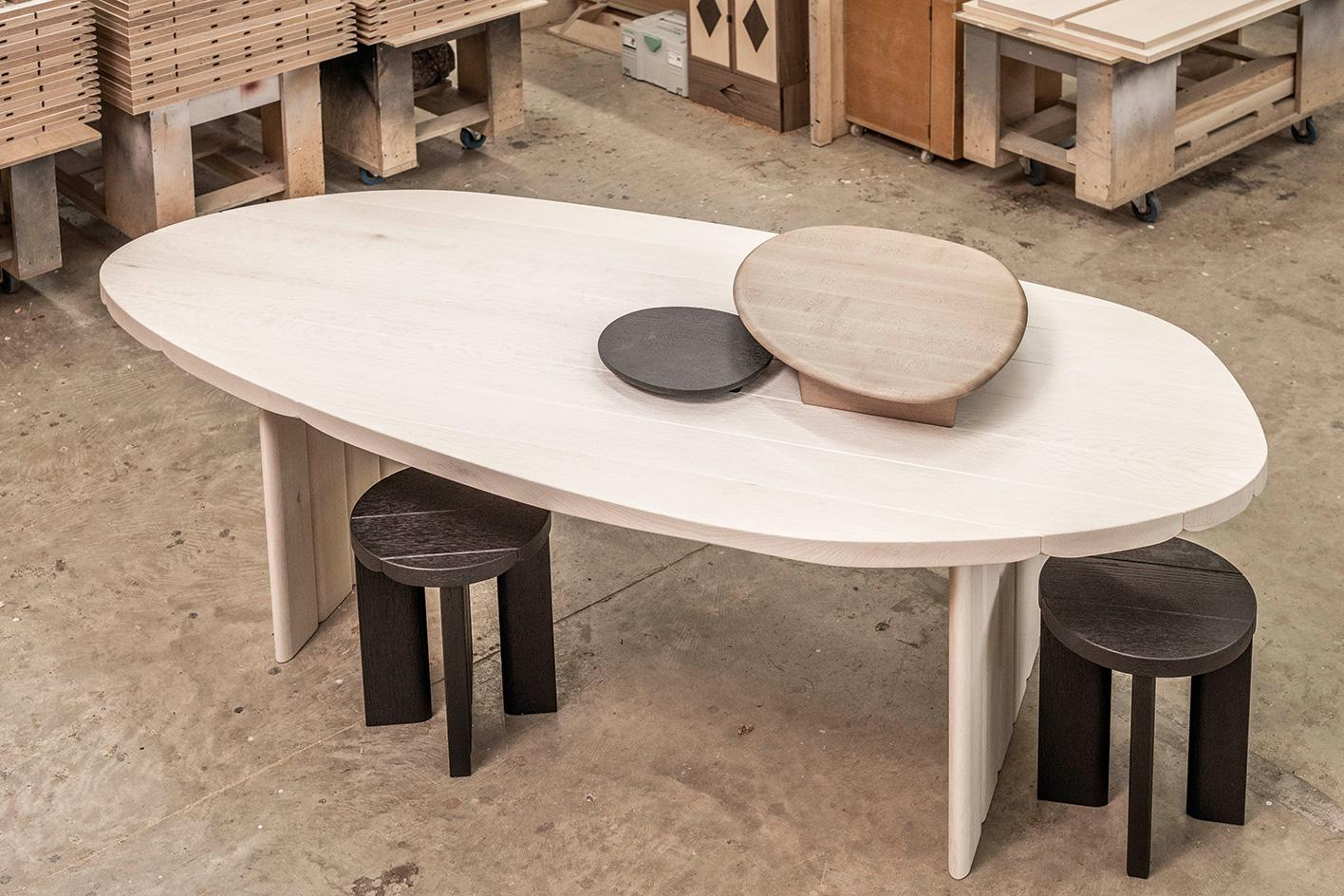 Sebastian Herkner's bleached red oak table, with tracks to allow trays, seen here in scorched red oak and ammonia-fumed maple, to slide along it