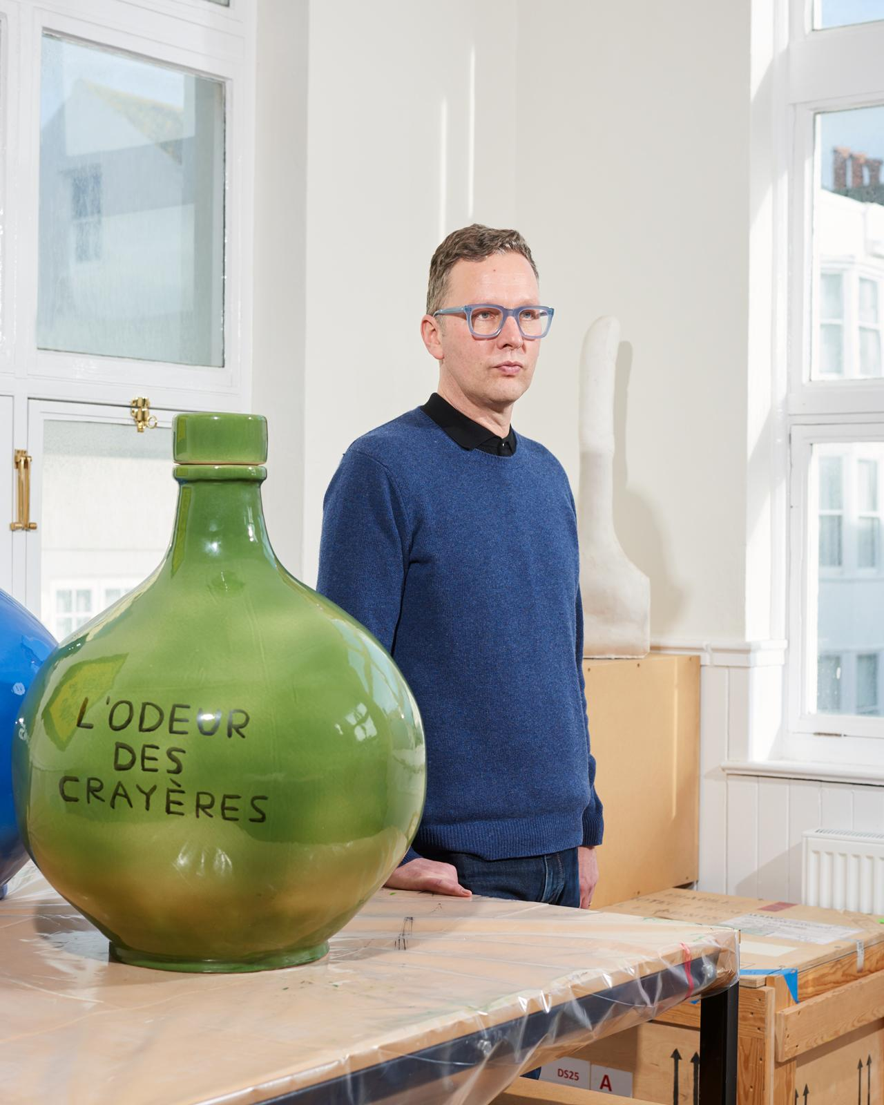 David Shrigley in his Brighton studio with ceramic vessel from his collaboration with Ruinart