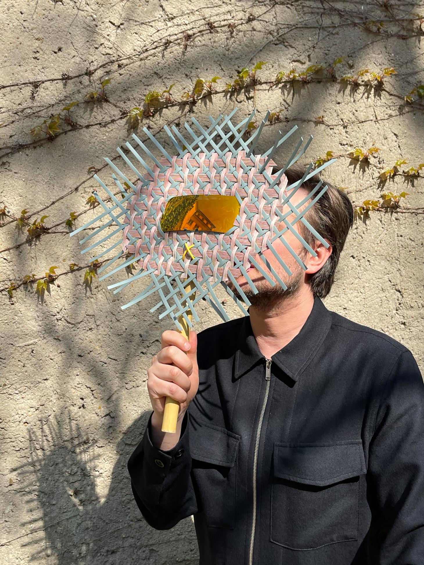 A portrait of German designer Sebastian Herkner whose face is hidden by a round fan woven with pink and light blue cord