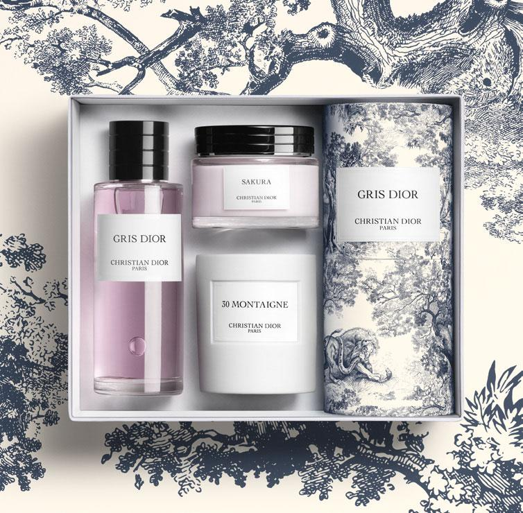 purple Gris Dior perfume in box with candle and body cream against blue Toile de Jolie background