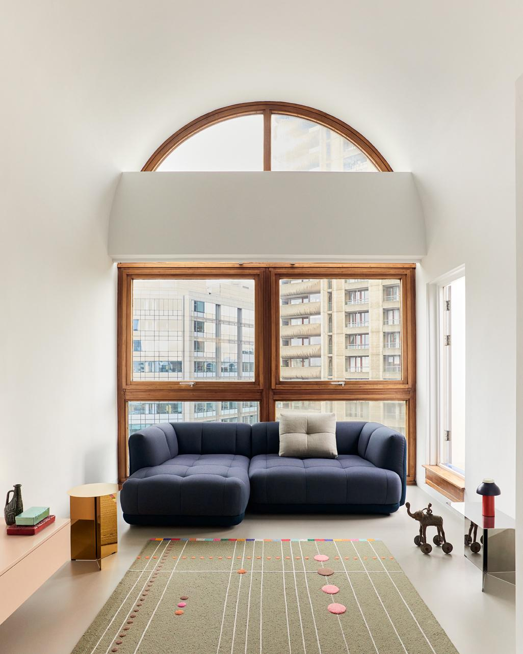 The Quilton sofa by Doshi Levien for Hay in blue, photographed at the Barbican in London against a wide window from which the building's architecture is visible