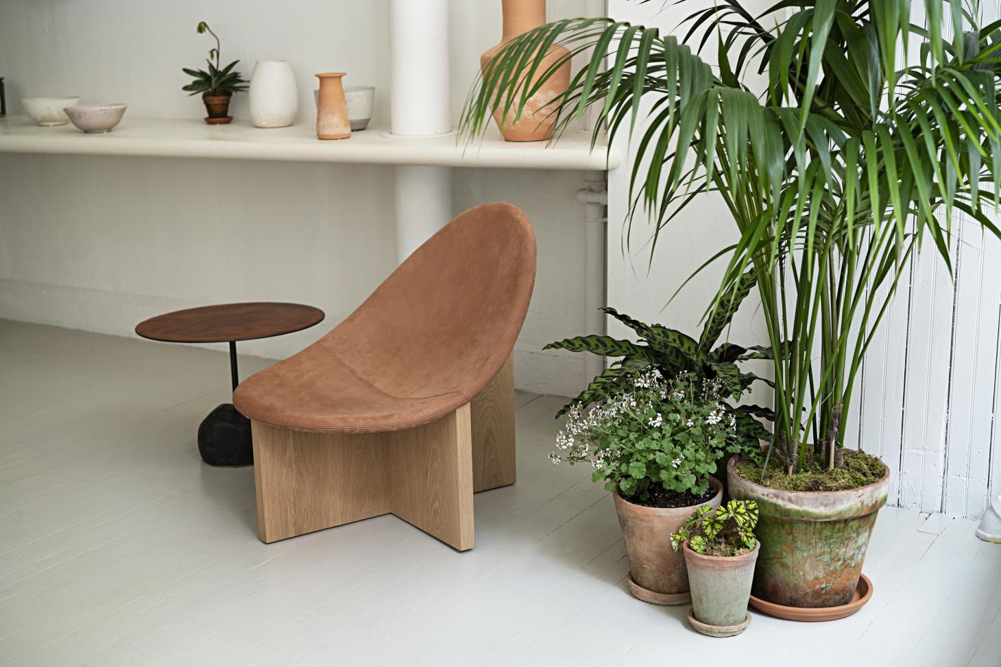 The 'Nido' chair by Estudio Persona and 'Grounded Circle' table by Stephen Kenn. On the shelves in the background are ceramics by Emilie Halpern