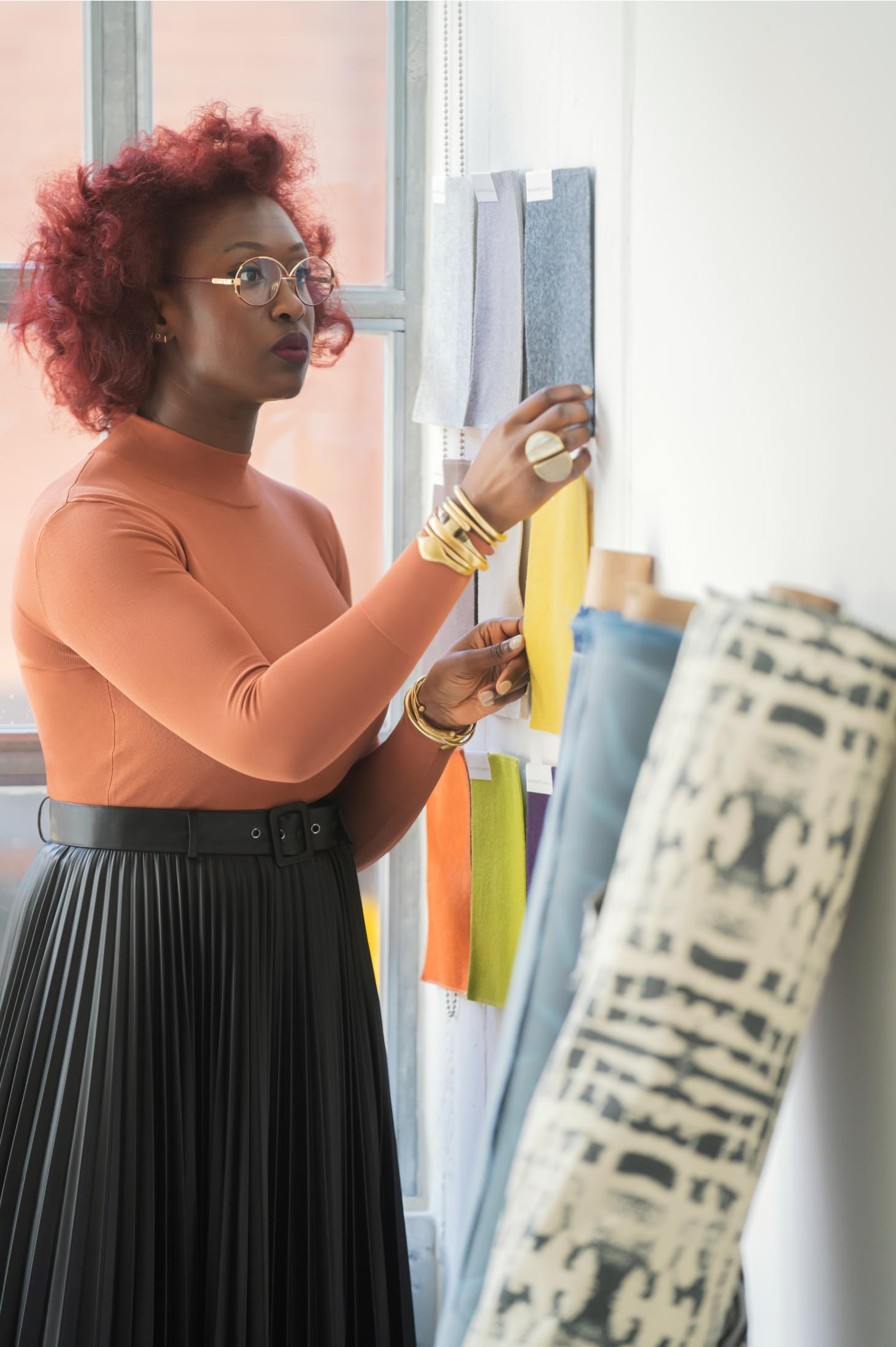 Portrait of designer Chrissa Amuah looking at fabric samples from her collection of upholstery textiles for Bernhardt