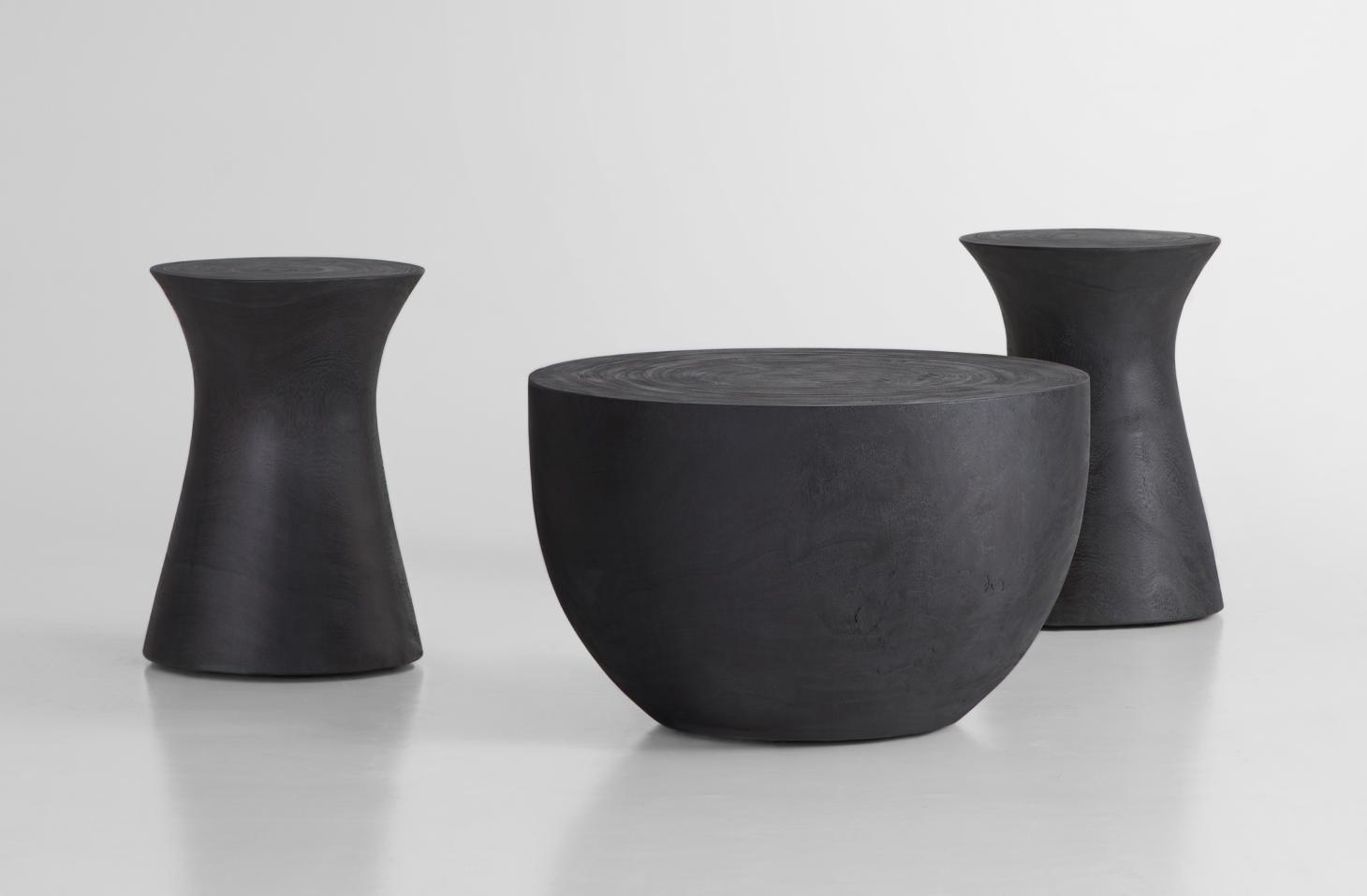 Small monolithic tables in black wood