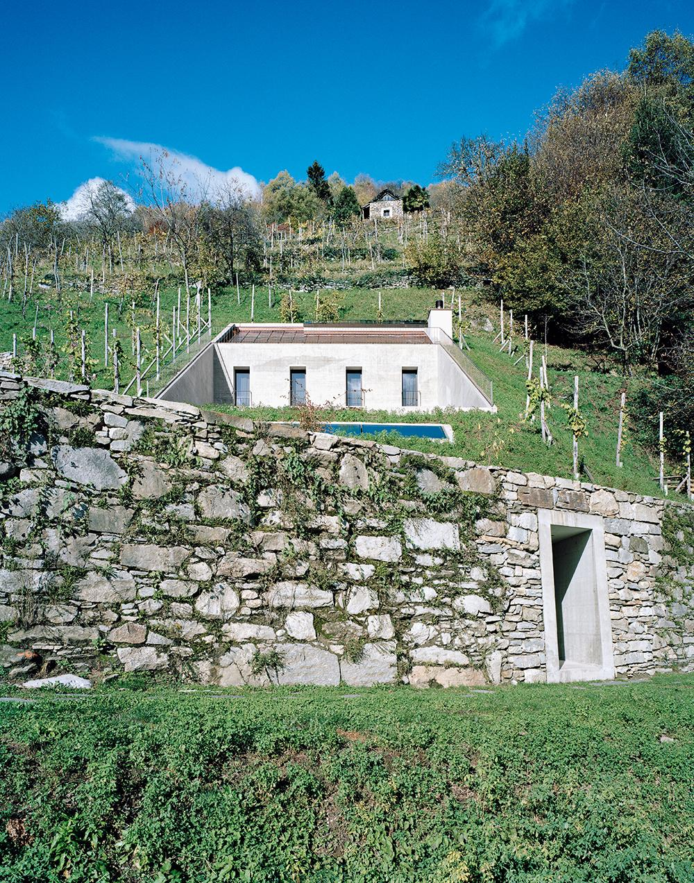 Exterior of Casa Bula, Ticino, Switzerland, accessed via a stone wall