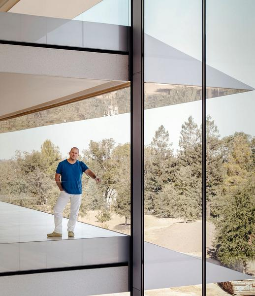 Apple's chief design officer Jony Ive in the brand's new HQ, with a glimpse of the 175-acre Apple Park in the background
