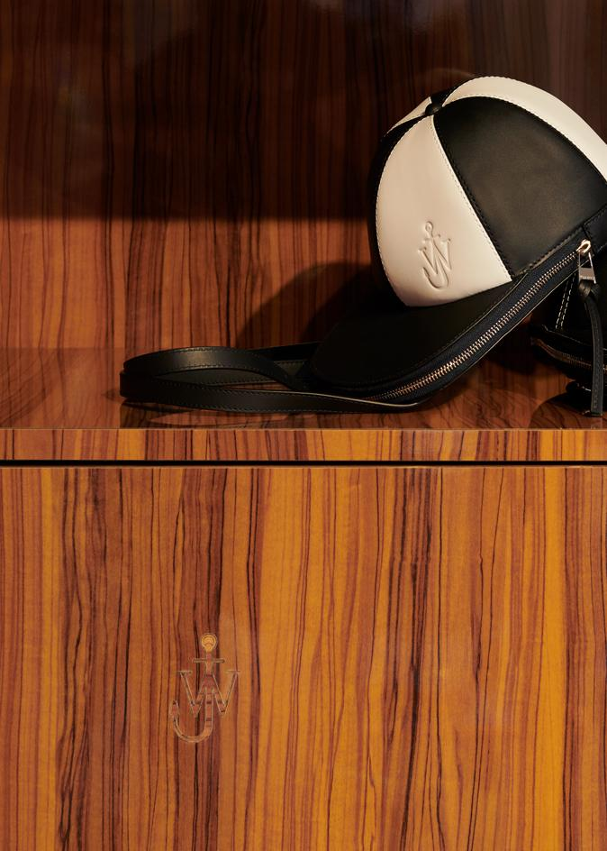 A JW Anderson Cap bag sits on a wooden shelf, with a carved JW Anderson logo