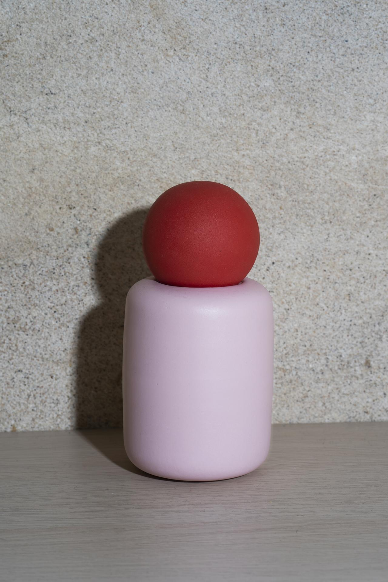 pink vase with red sphere on top