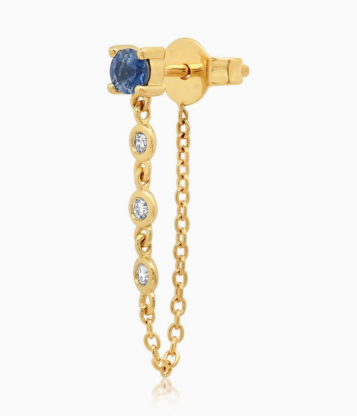 Gold earring with a sapphire stud and chain dangling down
