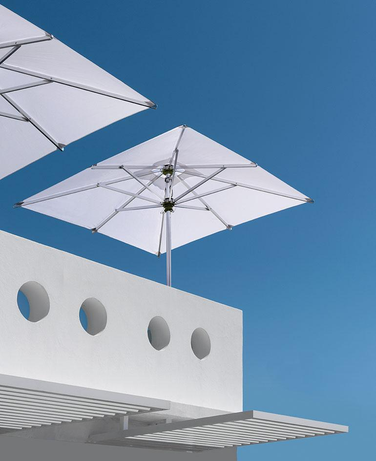 Two white parasols shot from below, shown against bright blue sky and on white modernist architecture