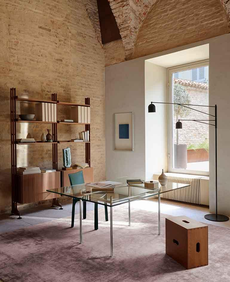 A room with vaulted brick ceiling featuring a wooden Infinito Bookcase by Franco Albini and Franca Helg on the wall