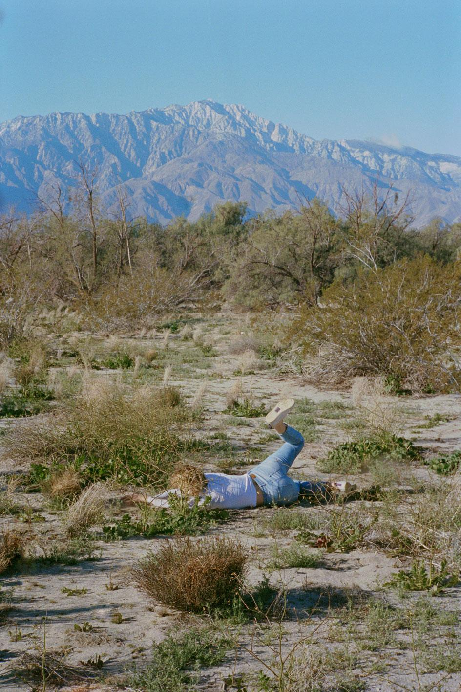 Image of a fallen figure on the ground with a mountainous backdrop. From Gabby Laurent's series Falling 2018-2020