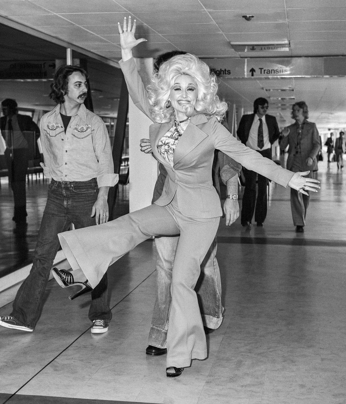 Black and white image of Dolly Parton in a suit doing a kick