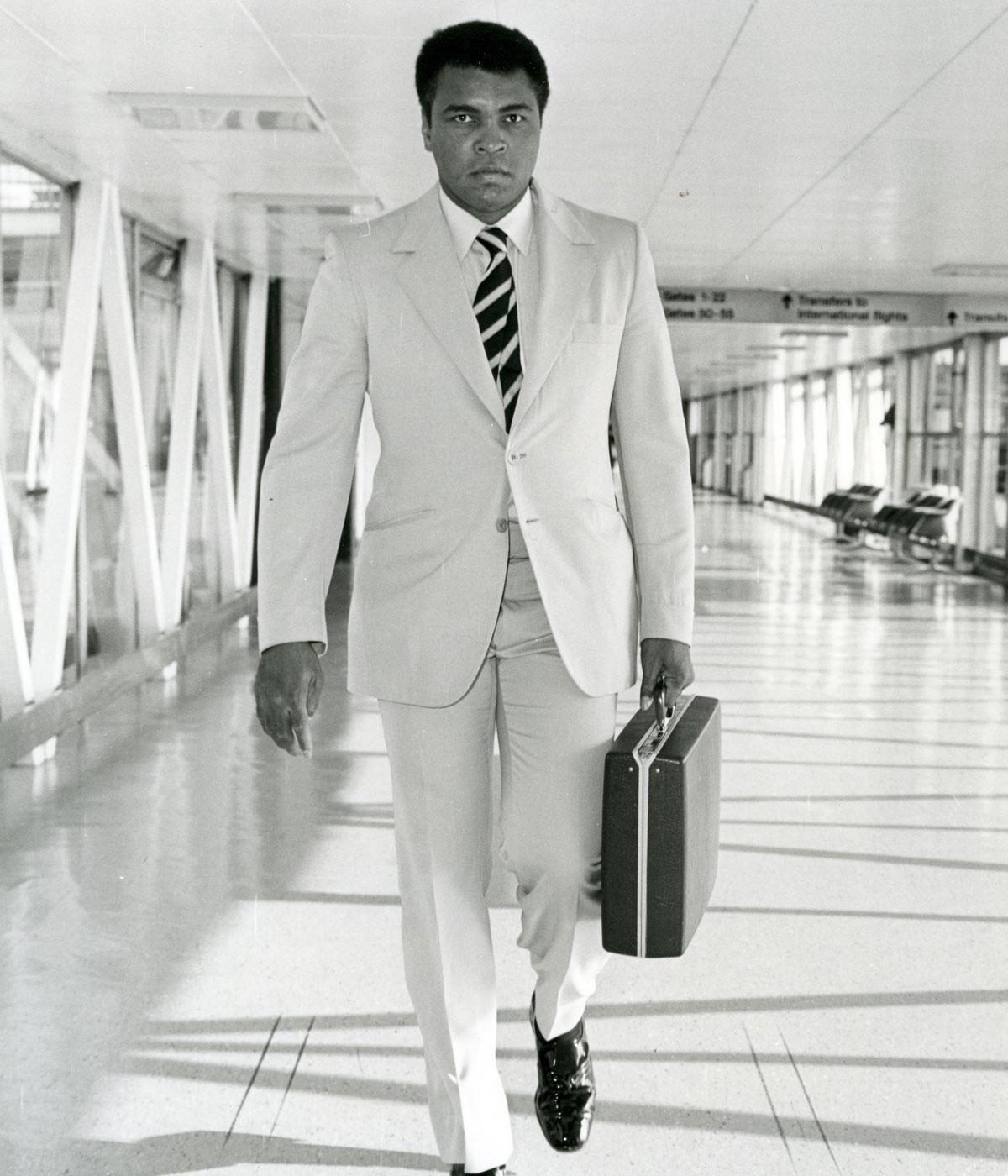 black and white photo of moahmmed ali in a suit holding a briefcase