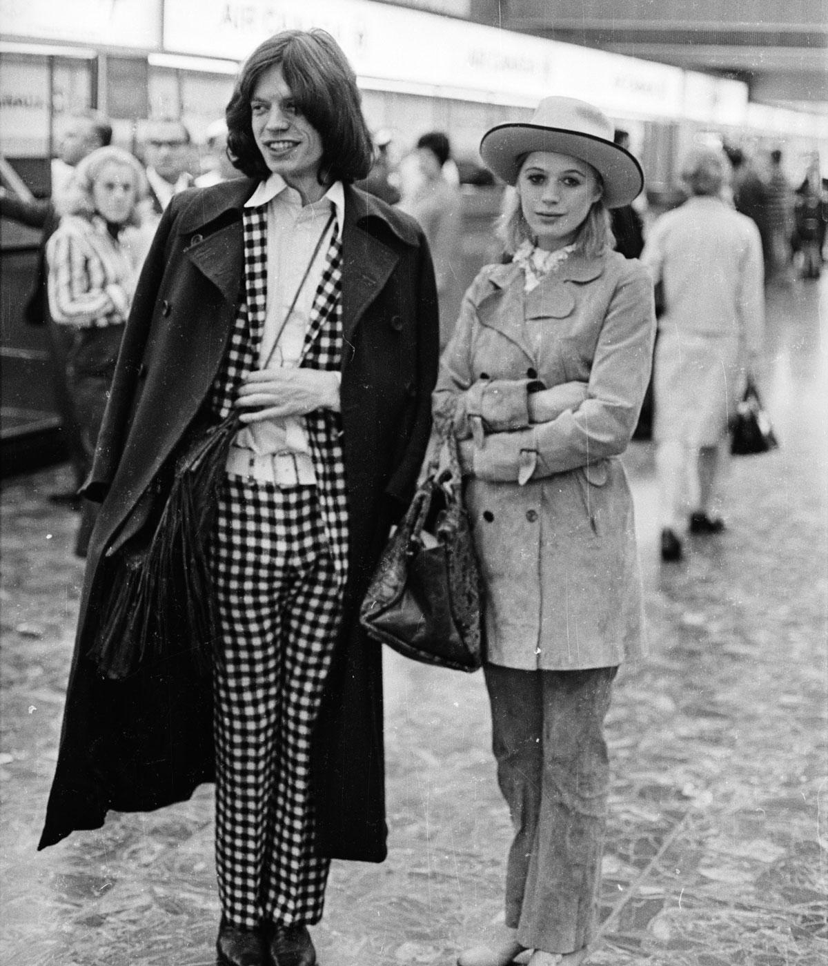 black and white image of mick jones and marianne faithful standing in an airport