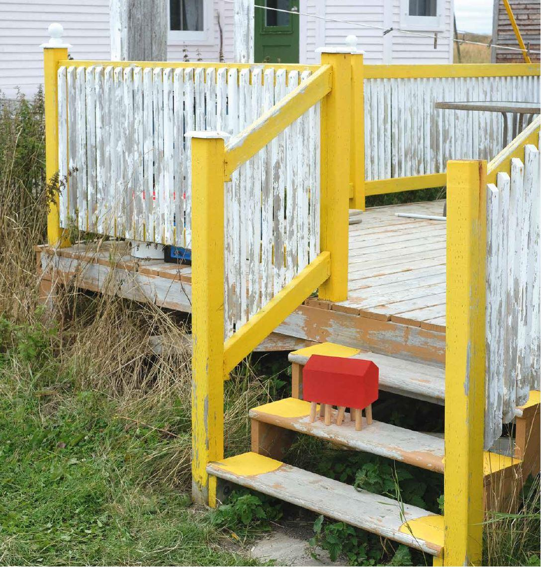 Small wooden house game photographed on the stairs of a balcony on Fogo Island