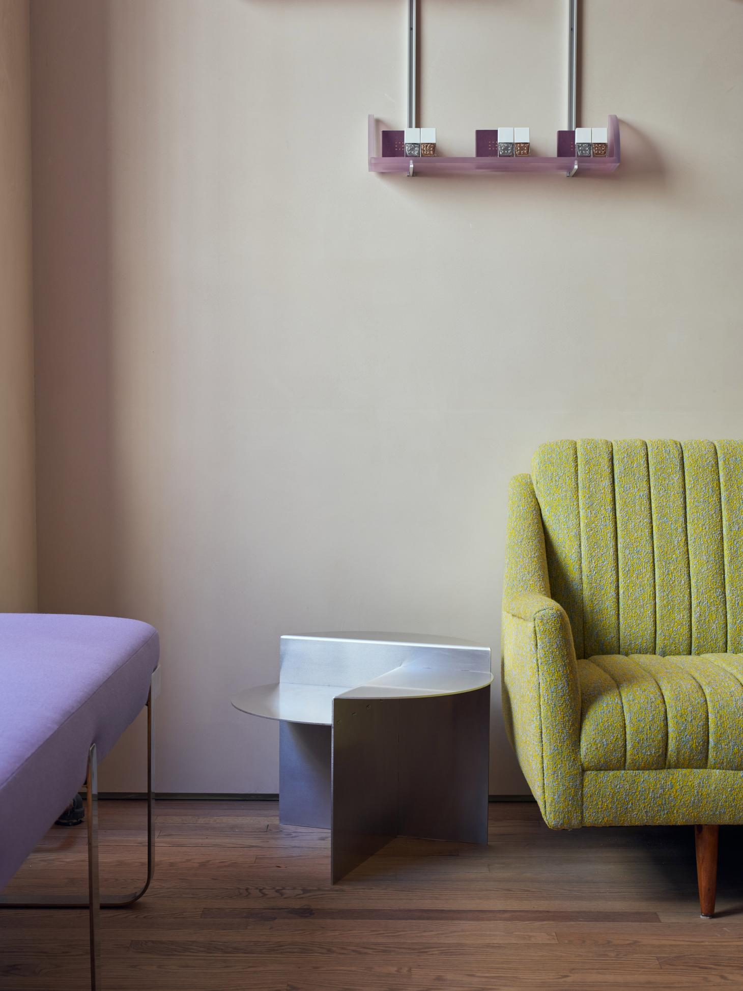 A nail salon features a yellow sofa and a purple wool bench