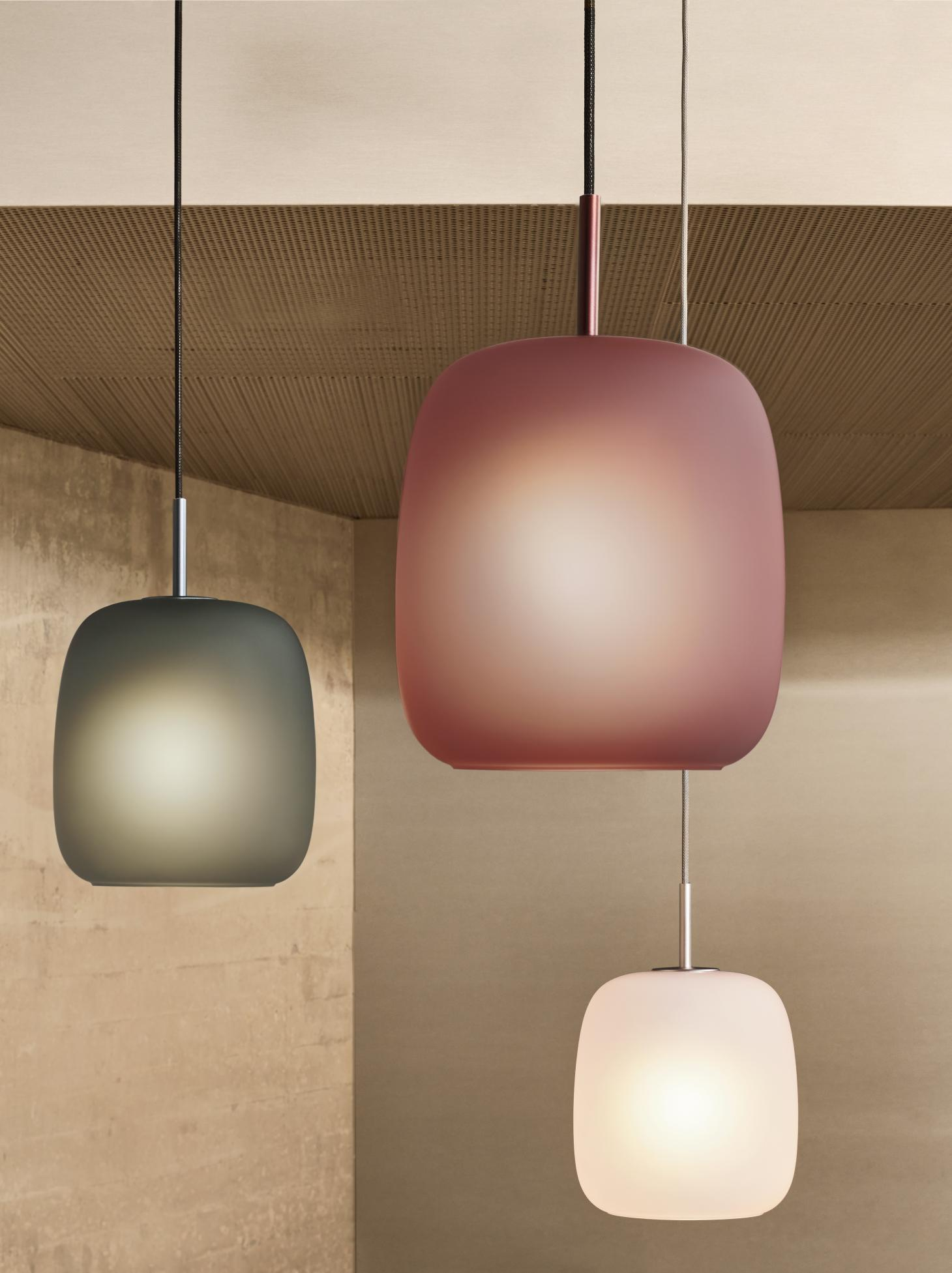 Three pendant lights with pink, green and white frosted glass shades