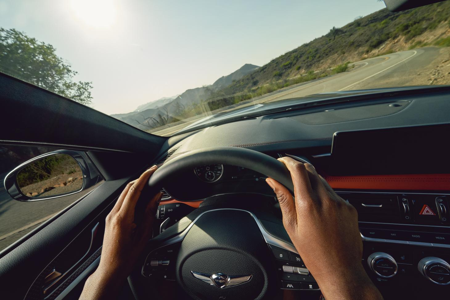 Genesis G70 car, interior image with driver's hands seen on steering wheel