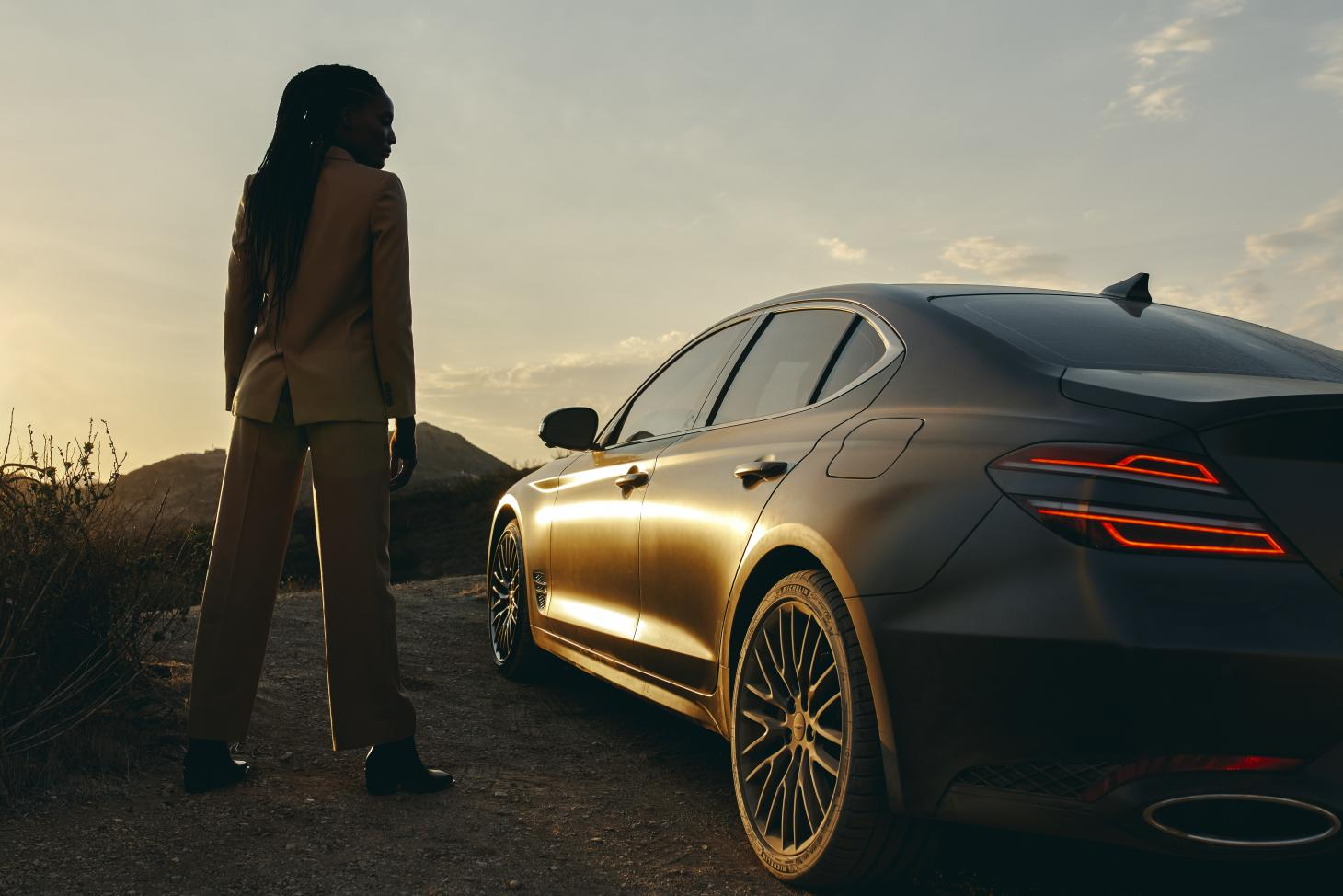 Genesis G70 car exterior image at sunset with woman standing to left of vehicle