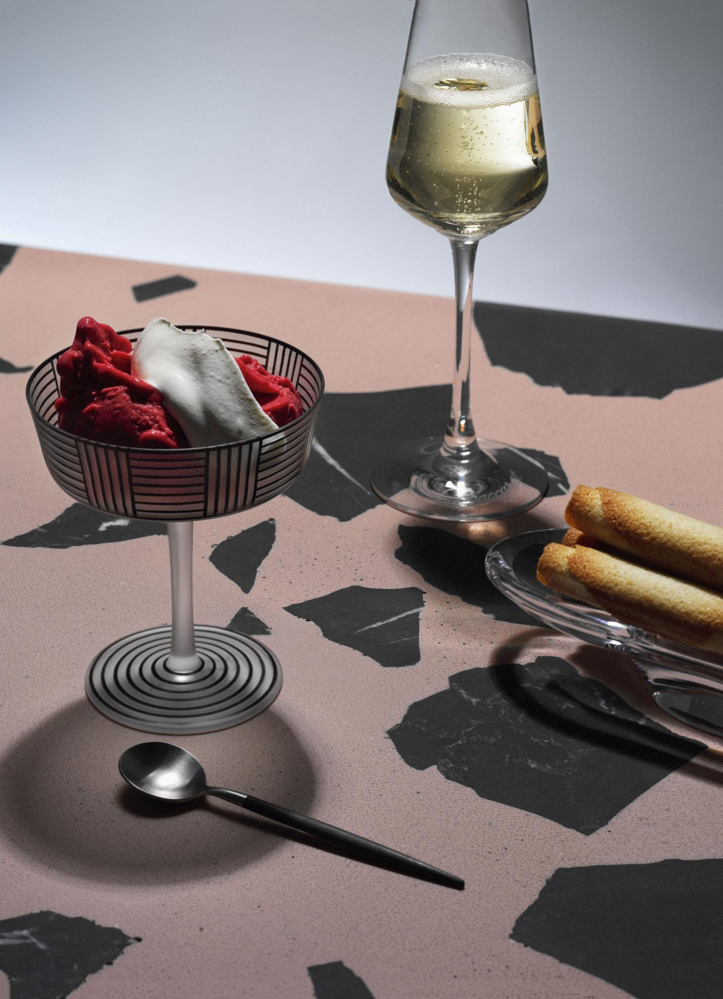 raspberry sorbet and gelato in glass cup on pink countertop next to glass of champagne