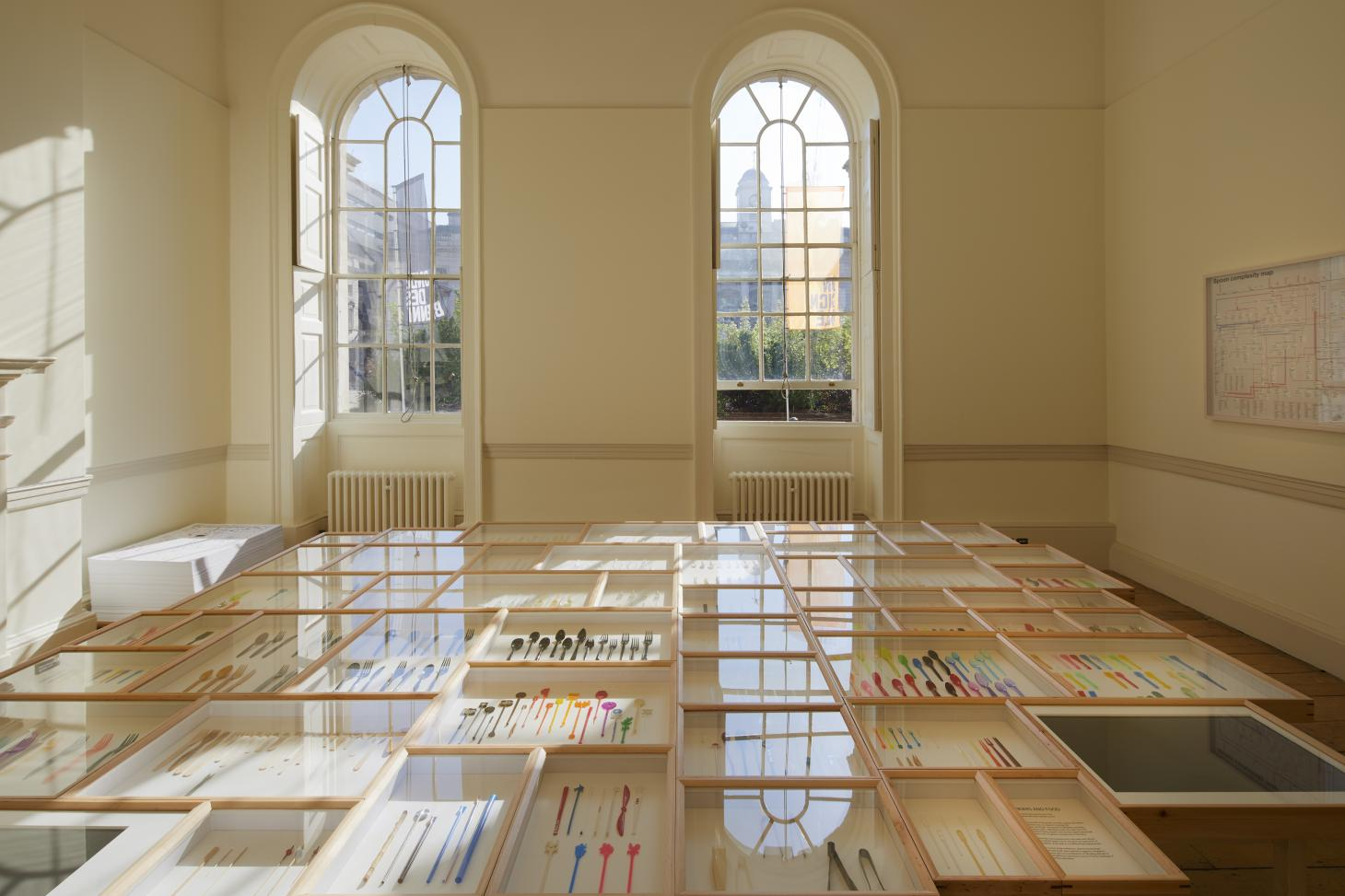 A room with arched windows in Somerset House, with installation of colourful plastic spoons in wooden and glass cases as part of the German Pavilion at London Design Biennale